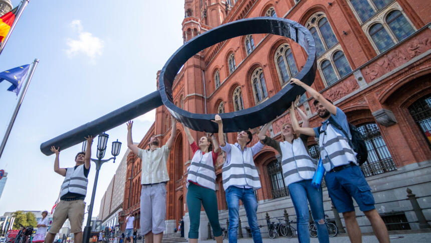 Mehrere Menschen halten vor dem Roten Rathaus eine überdimensionale Lupe hoch.