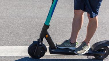 Beine einer Person auf E-Scooter