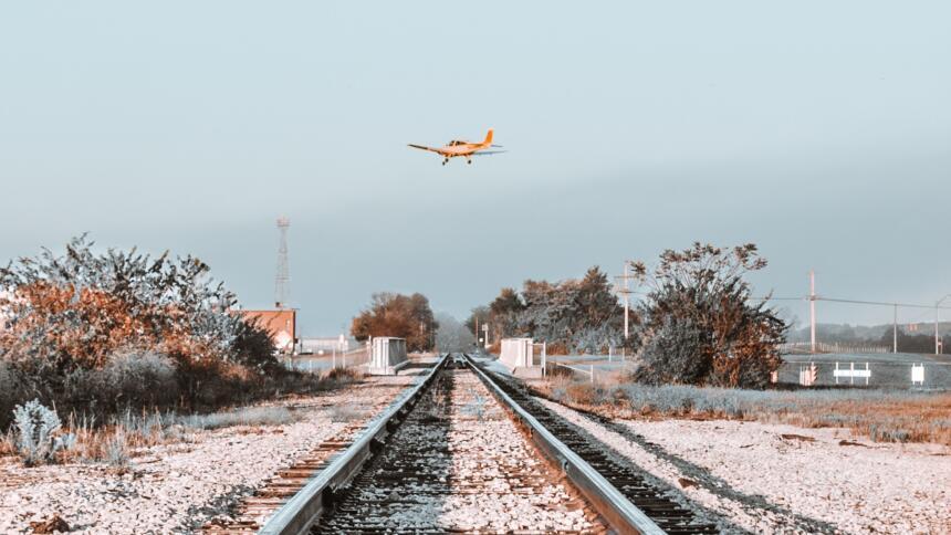 Flugzeug fliegt über Bahnschienen