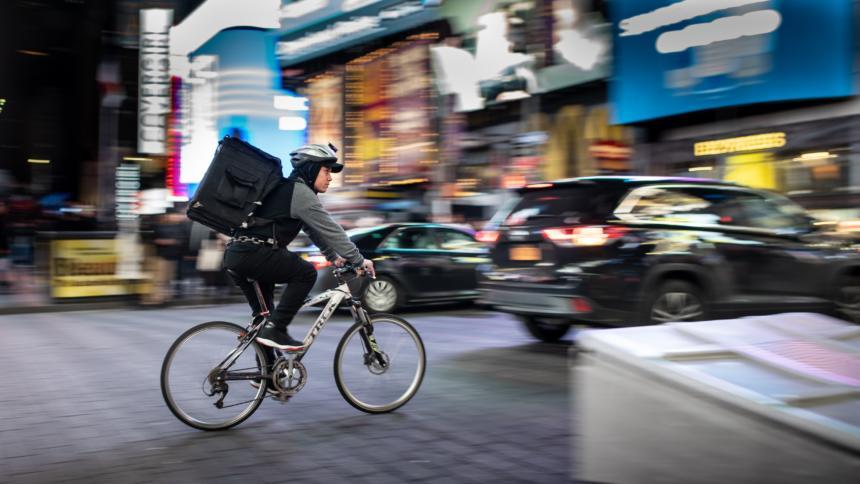 Ein schwarz gekleideter Fahrradkurier zoomt durch den New Yorker Times Square, aber den erkennt man nicht so wirklich