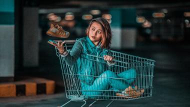 Frau sitzt in einem Einkaufswagen