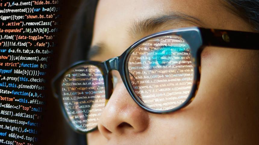 Frau mit Brille in der sich Code spiegelt