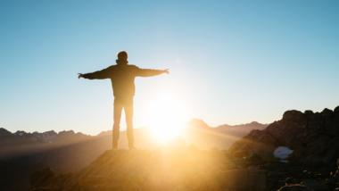 Mensch steht auf Berggrat