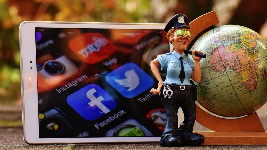 Polizistenfigur neben Smartphone und Spielzeug-Globus