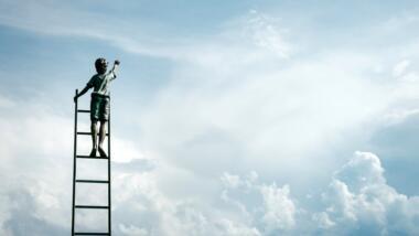 Ein Kind steht hoch oben auf einer Leiter