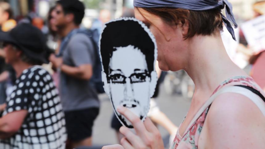 Demonstrantin hält ausgedrucktes Snowden-Gesicht