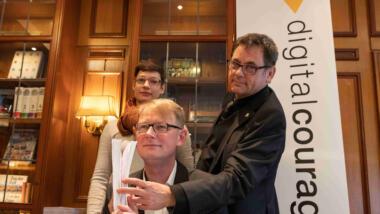 Der Beschwerdeführer Prof. Roggenkamp und zwei Mitglieder des Vereins Digitalcourage halten die Beschwerde in der Hand.