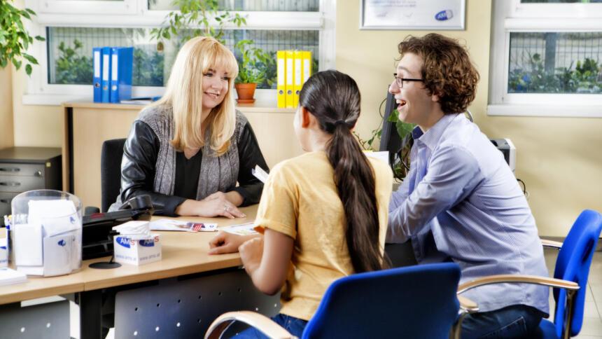 Jugendliche sitzen vor AMS-Beraterin