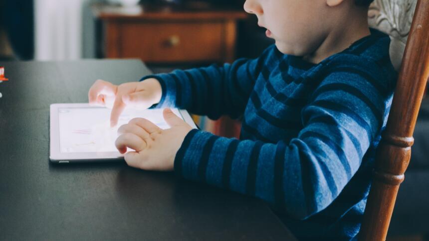 Ein Kind sitzt an einem Tisch und nutzt einen Tablet-Computer.