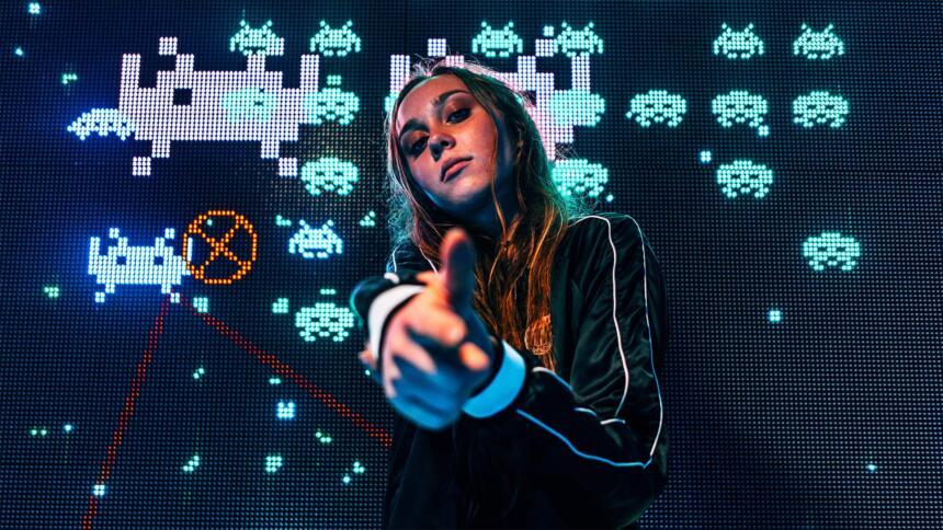 Frau deutet mit der Hand eine Pistole an, hinter ihr ein Bildschirm mit einem alten Computerspiel