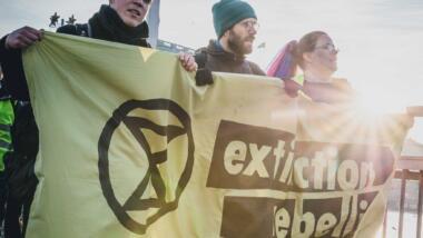 """Menschen tragen ein Transparent mit der Aufschrift """"Extinction Rebellion"""""""