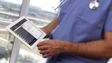 Ein Mensch im Arztkittel mit Tablet