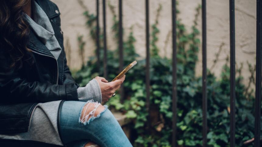 Frau sitzt mit Beinen übereinander geschlagen, i der Hand ein Smartphone