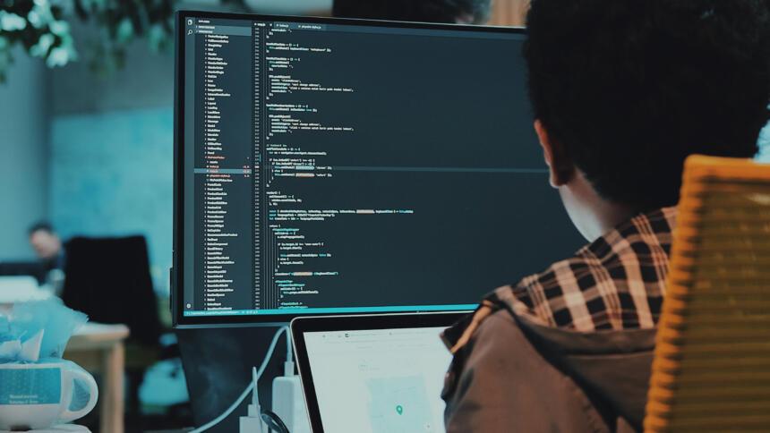 Mensch, der vor einem Computer sitzt und programmiert.