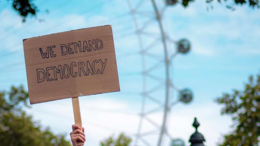 """Schild mit der Aufschrift """"We demand Democracy"""""""