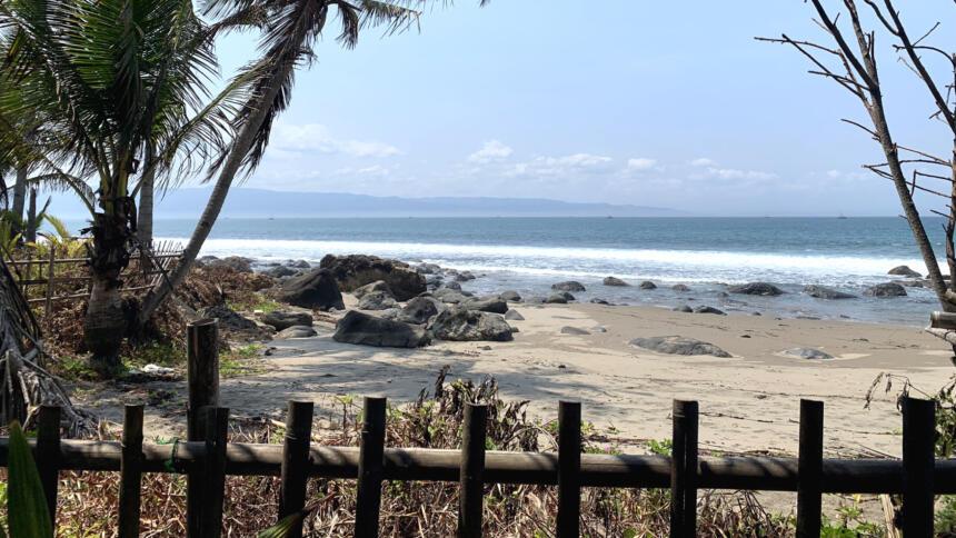 Strand mit Palmen, im Vordergrund ein einfacher Holzzaun