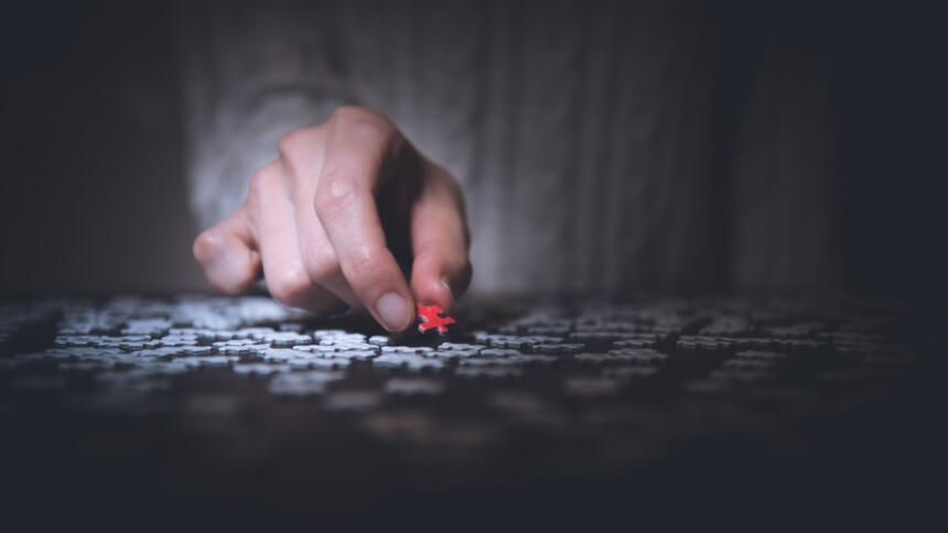 Eine Hand hält ein rotes Puzzleteil