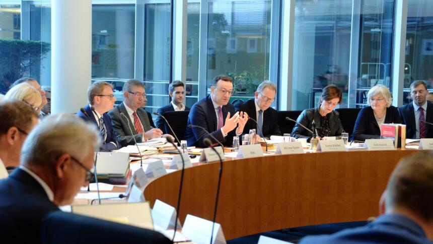 Jens Spahn gestikuliert vor dem Gesundheits-Ausschuss. Neben ihm sitzen weitere Politiker:innen.