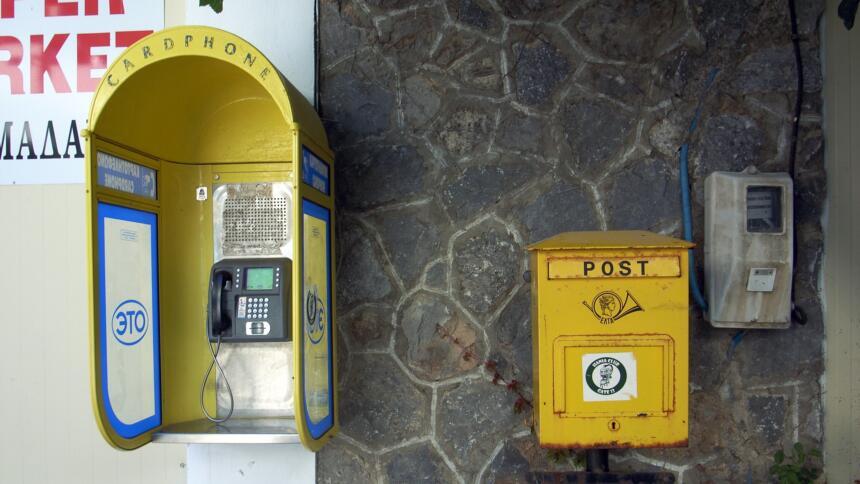 Ein Briefkasten neben einem Münzfernsprecher