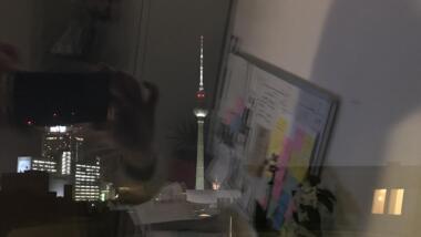 Berliner Fernsehturm aus einem Fenster, in dem man die Spiegelung sieht