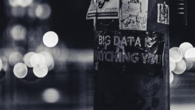 """Ein Laternenpfosten mit einem Sticker mit dem Spruch """"Big Data is watching you"""" ist auf dem Bild."""