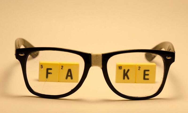 Eine Brille mit geklebtem Steg liegt auf einer orangenen Unterlage. Durch die Brillengläser sieht man das Wort FAKE, gelegt aus Scrabbel-Steinen.