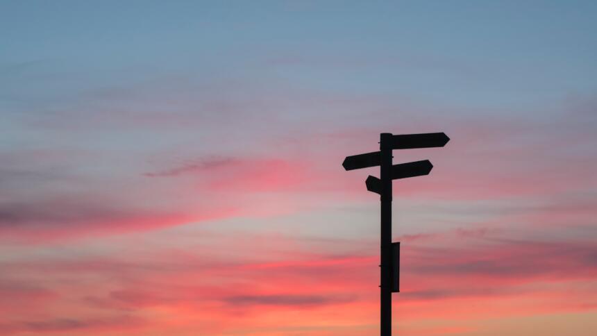 Ein Wegweiser mit vier Schildern, die in verschiedene Richtungen zeigen vor einem Abendhimmel ist zu sehen.