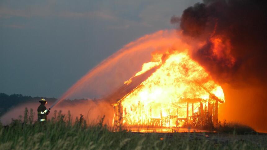 Feuerwehrmensch löscht brennendes Haus