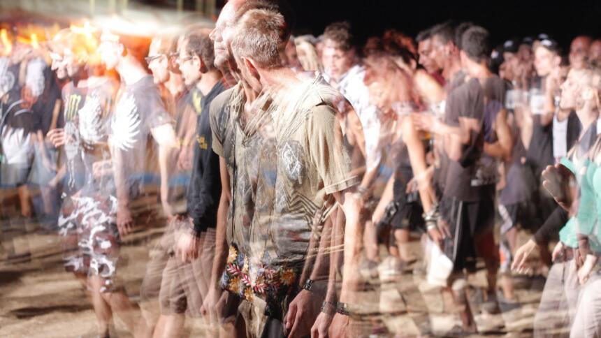Man sieht Menschen in einer größeren Menge, die alle sehr verschwommene Konturen haben.