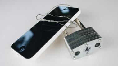 ein Smartphone, das mit Draht umwickelt ist. an dem draht ist ein vorhängeschluss befestigt.