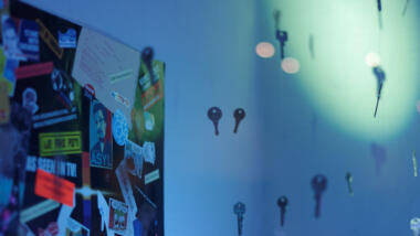 """Die Ecke eines blau ausgeleuchteten Raumes ist zu sehen, an der linken Wand hängt eine Pinnwand mit vielen Stickern (einer davon ist ein """"Asyl für Snowden""""-Sticker). Davor scheinen Schlüssel in der Luft zu schweben, die an Schnüren an der Decke aufgehängt sind."""