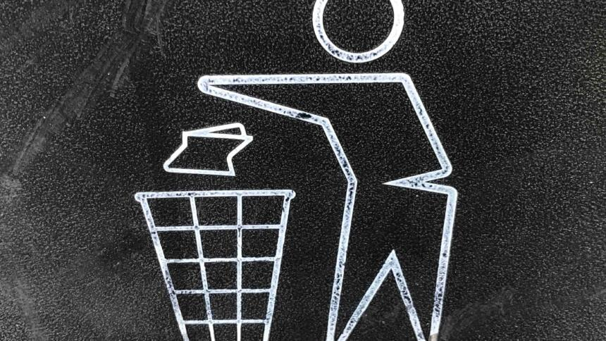 Man sieht ein Piktogramm auf schwarzem Hintergrund: Das Symbol für Wegwerfen beziehungsweise in den Müll tun.