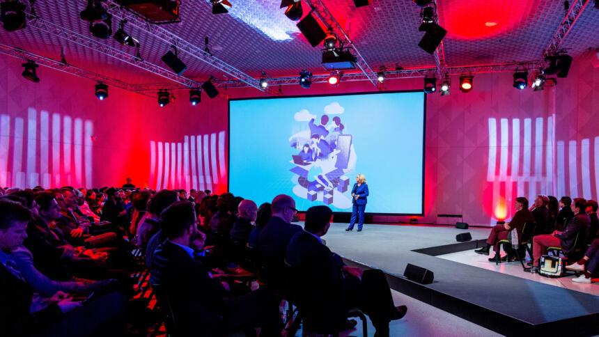 Ein großer Saal, in roten Farben beleuchtet. Zentral ist eine große Bühne, auf der die Ministerin Schulze vor einer Leinwand steht und eine Rede hält. Links und rechts davon sitzen Menschen in schicker Kleidung auf Stühlen im Publikum.