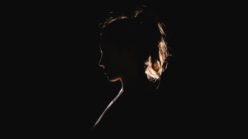 Die Silhouette einer Frau mit Pferdeschwanz-Frisur im Profil. Sie ist kaum zu erkennen, weil sie von hinten angeleuchtet wird. Lediglich ihre Umrisse heben sie vom ebenfalls schwarzen Hintergrund ab.