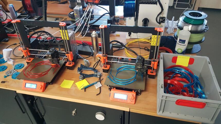 Eine Werkbank, auf der ein 3D-Drucker steht und viel Zubehör herumliegt.