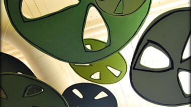 Eine Nahaufnahme mehrerer aus Pappe ausgeschnittener Zahnräder in verschiedenen Grüntönen.
