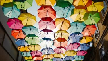 Eine Fotomontage: Von unten blickt man auf viele bunte Regenschirme, die zwischen zwei Häusern zu schweben scheinen und so quasi ein Dach bilden.
