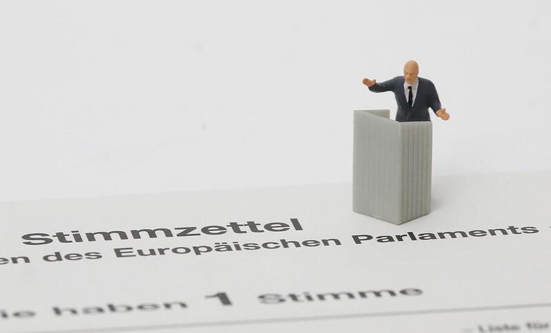 Eine kleine Figur eines Mannes im Anzug hinter einem Rednerpult steht auf einem Stimmzettel, der laut Aufschrift zu den EU-Wahlen gehört.