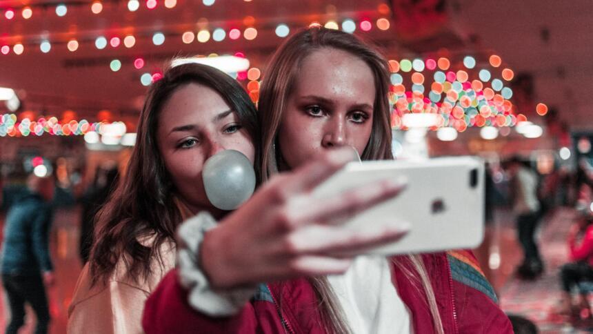 Zwei junge Frauen machen ein Selfie vor Kirmenhintergrund