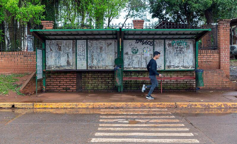 Eine Bushaltestelle, an der ein Mann vorbeirennt.