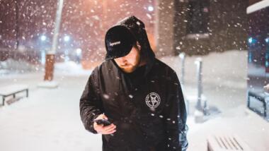 Mann schaut im Schnee auf sein Smartphone