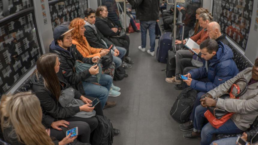 Menschen mit Smartphones in einer U-Bahn.