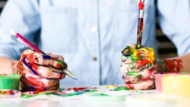 Mann im Hemd am Schreibtisch mit farbverschmierten Händen, Stift und Pinsel in der Hand.