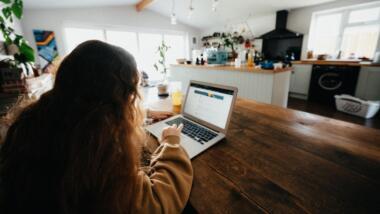 Kind sitz in großem Raum an einem Laptop und arbeitet.