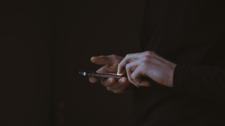 Nahaufnahme eines Smartphones, in der Hand einer Person vor schwarzem Hintergrund.