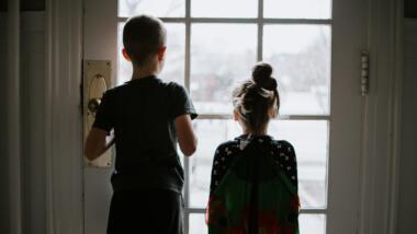 Junge und Mädchen stehen vor geschlossener Tür und schauen nach draußen.