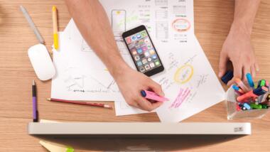 Schreibtisch von oben mit Computer, Smartphone, Papier und Stiften