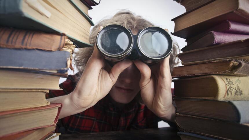 Person mit Fernglas zwischen zwei Bücherstapeln