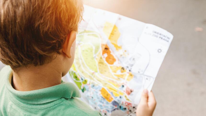 Man sieht den Hinterkopf eines Jungen, der eine unscharfe Landkarte in der Hand hält und darauf schaut.