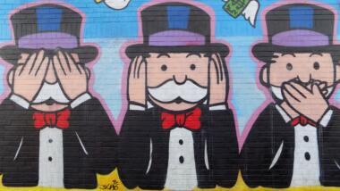 Graffity des Monopoly-Männchens mit Anzug, Fliege und Hut, hält sich einmal die Augen zu, einmal die Ohren und einmal den Mund.